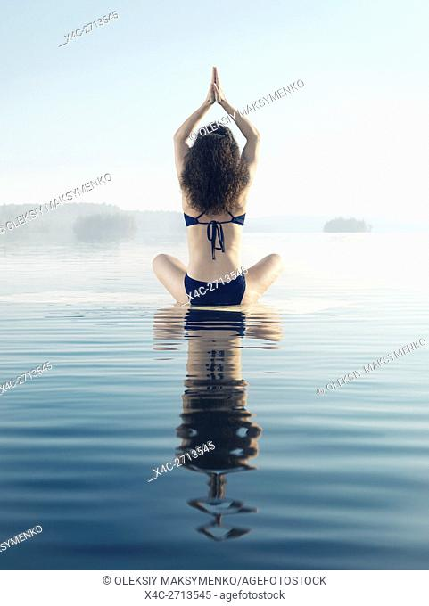 Artistic photo of a woman meditating on a platform in calm water on a misty lake in early morning during sunrise. Yoga meditation. Rear view