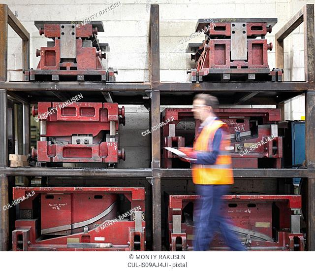 Worker with clipboard walking past press moulds in sheet metal factory
