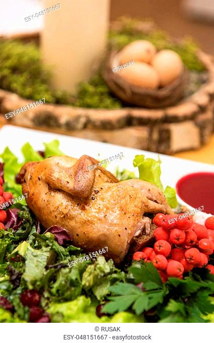 quail roasted with sweet and sour cranberry sauce decorated with rowanberry