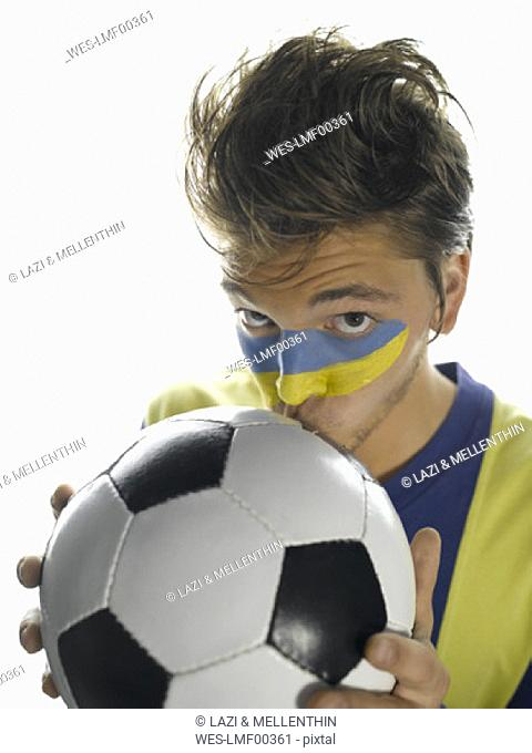 Young man with Ukrainian flag painted on face, kissing soccer ball, elevated view
