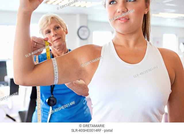 Trainer measuring girls arm in gym