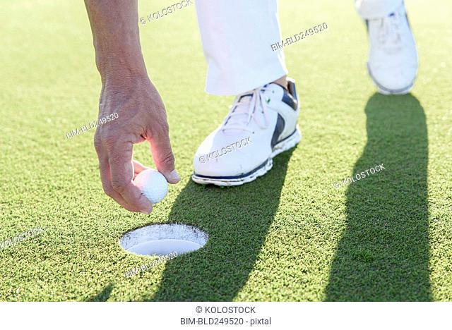 Hispanic man retrieving golf ball from hole on golf course
