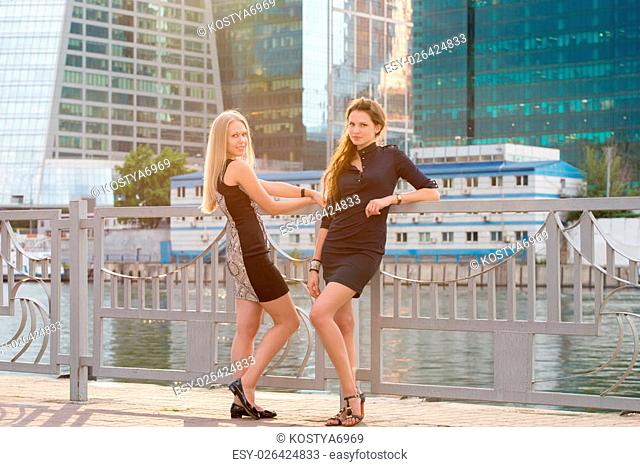 Two young beautiful girls in dress stroll along the river on the waterfront near skyscrapers