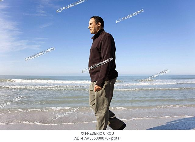 Mature man walking on beach