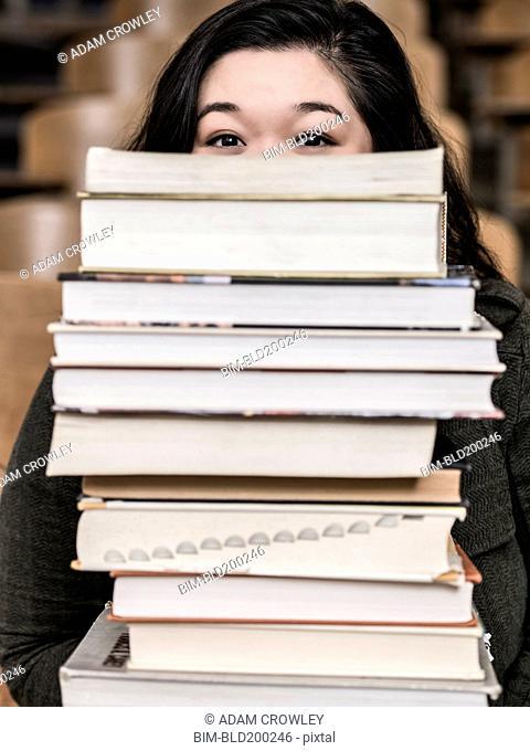 Korean student holding stack of books