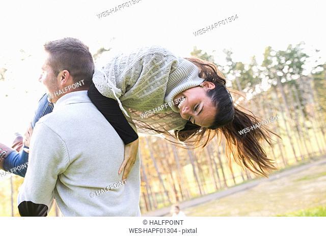 Playful man carrying girlfriend outdoors