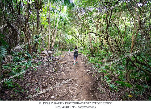 Mother and her son hiking in a natural area at the Hauula Loop Trail on Oahu Hawaii
