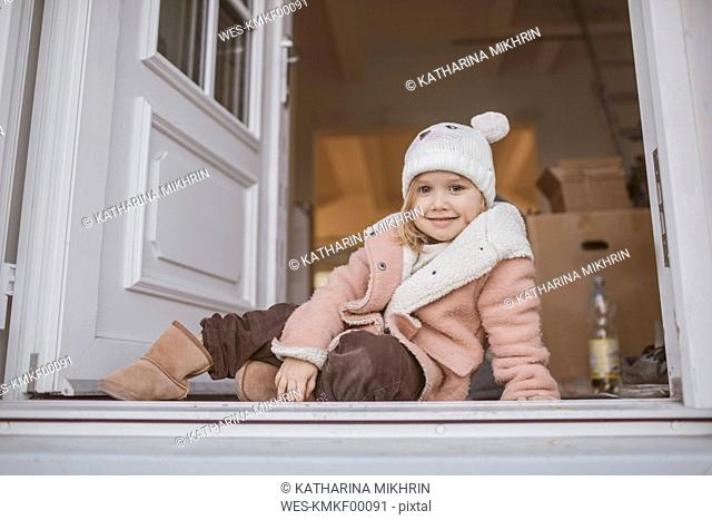 Young girl sitting in entrance, cardboard box