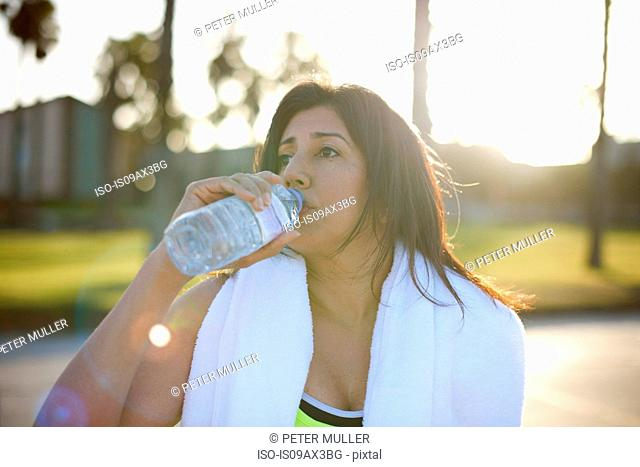 Woman with towel on shoulders drinking water from plastic bottle