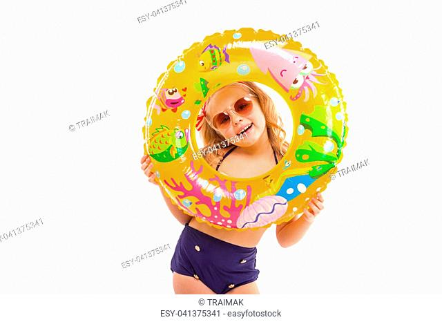 Isolated on white, pretty cute caucasian blonde girl in red striped bikini, blue bottoms, sunglasses and pink flower wreath hold colorful rubber ring near her...