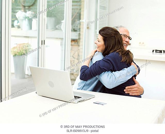 Mature couple using laptop, embracing