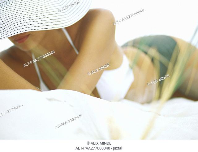 Woman lying on sand wearing bikini and sunhat