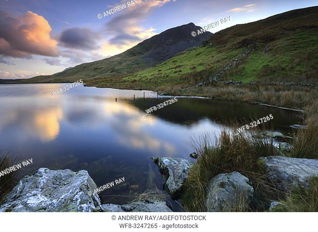 Sunset captured from the northern shore of Llyn Dywarchen in the Snowdonia National Park in North Wales, with the prominent peak of Y Garn in the distance