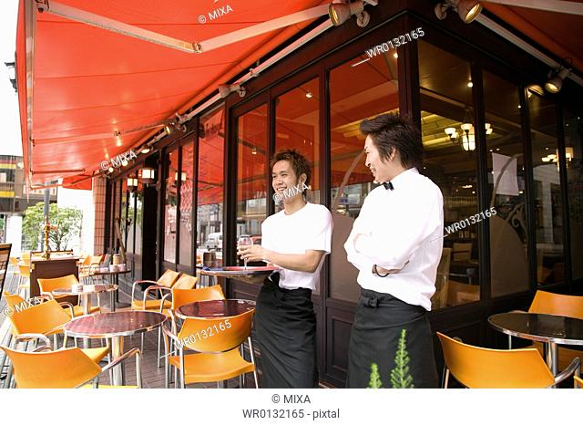 Two waiters standing in front of coffee shop