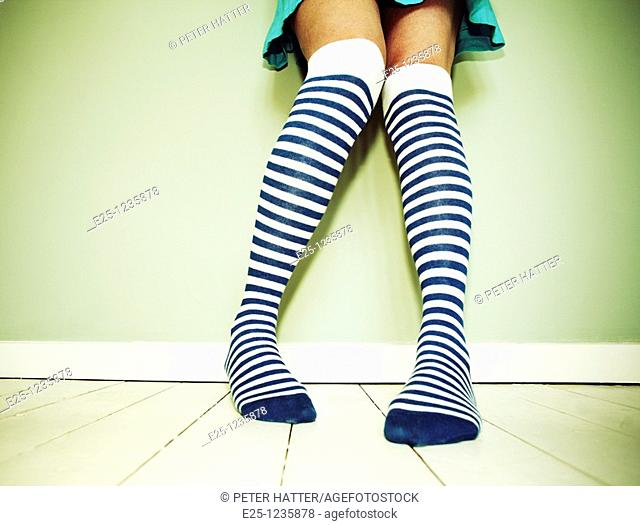Adult female wearing stripey socks stands against a wall on a wooden floor painted white