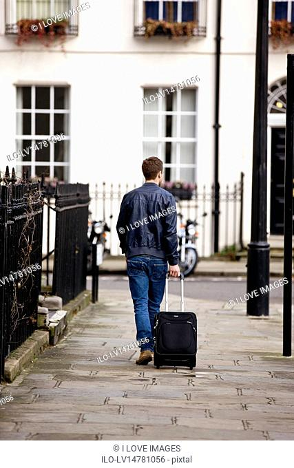 A young man pulling his suitcase in the street, back view