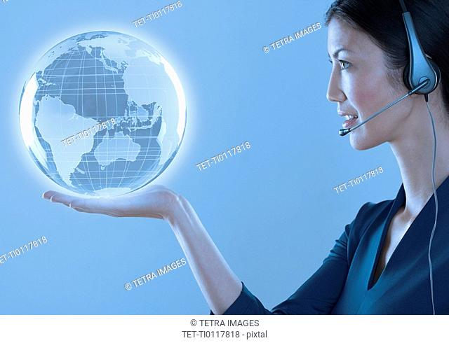 Woman with headset holding a globe