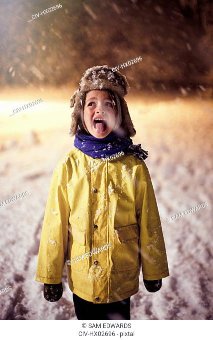 Boy in warm clothing sticking tongue out, tasting snow