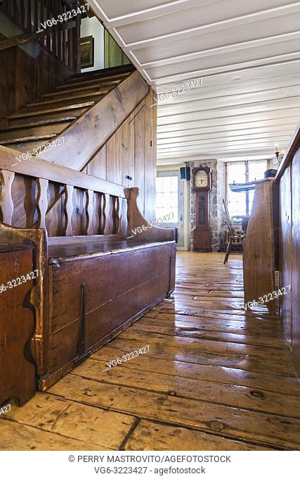 Old wooden antique beggar's bench on the ground floor inside an old 1835 fieldstone house