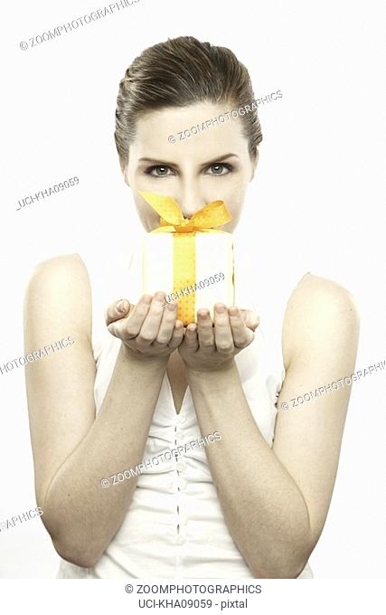 Woman holding gift wrapped present with bow