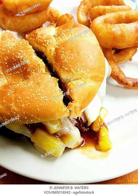 Close-up of a burger with cheese and pineapple