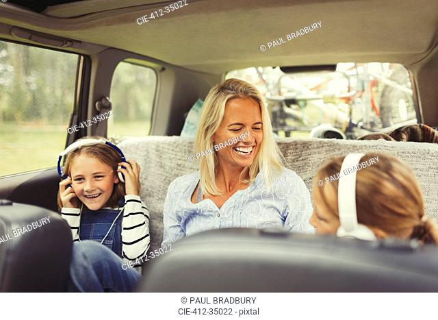 Laughing mother and daughters with headphones in back seat of car