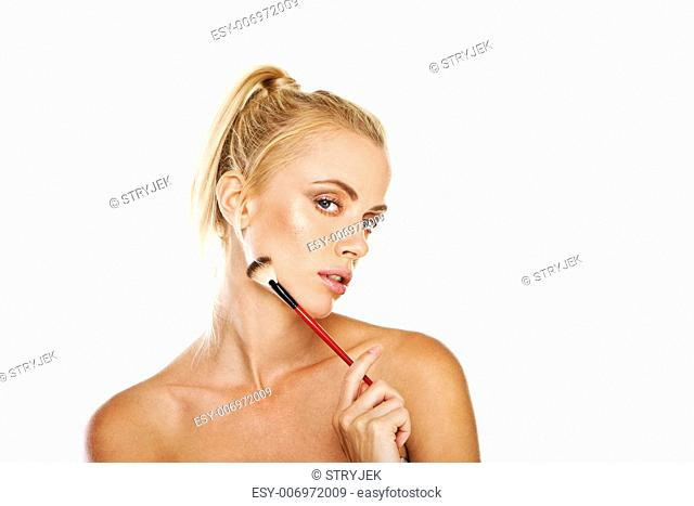 Beautiful woman with bare shoulders holding a cosmetics brush provocatively against her cheek