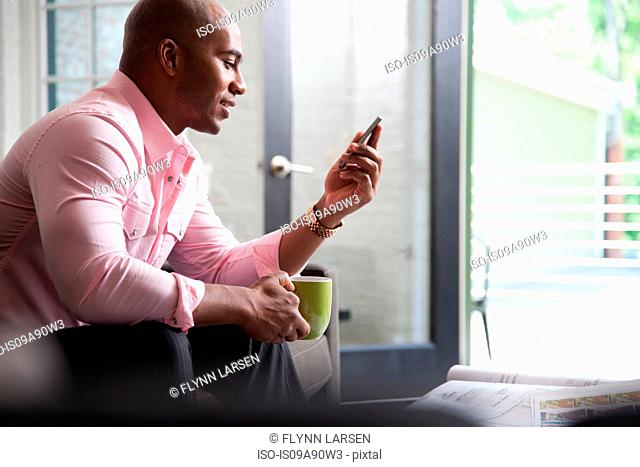 Mid adult man sitting on sofa looking at mobile phone