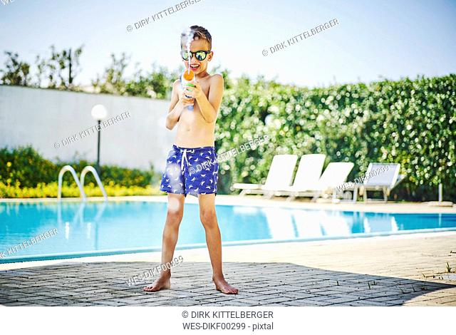 Boy at the poolside with water gun and sunglasses