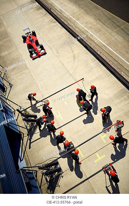 Pit crew ready for nearing formula one race car in pit lane