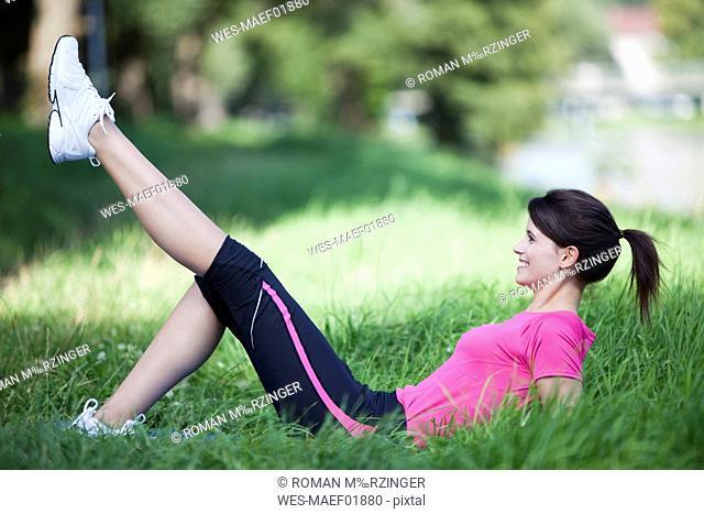 Germany, Bavaria, Woman stretching leg, lying on grass
