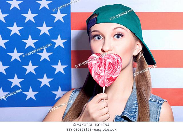 I love my country. Portrait of cheerful hipster woman holding candy in the shape of heart near her lips. She is standing near the usa flag and looking forward...