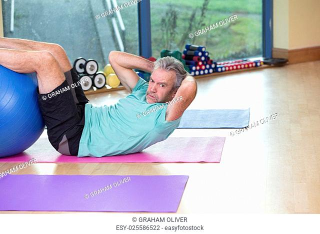 One senior man using gym equipment for sit-ups at the gym