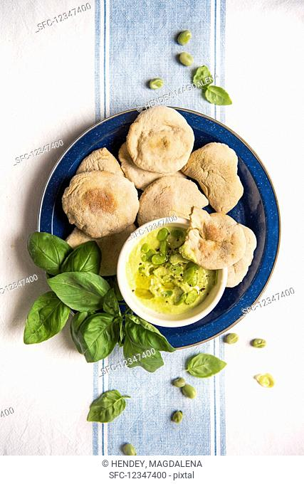 Mini pita breads with bean cream and basil