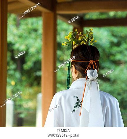 Rear view of female attendant walking at shrine