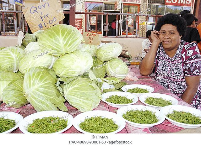Fiji, Viti Levu, Sigatoka, fijian woman in traditional dress selling cabbage and hot peppers in the market