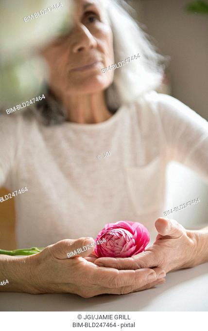 Older woman holding pink flower