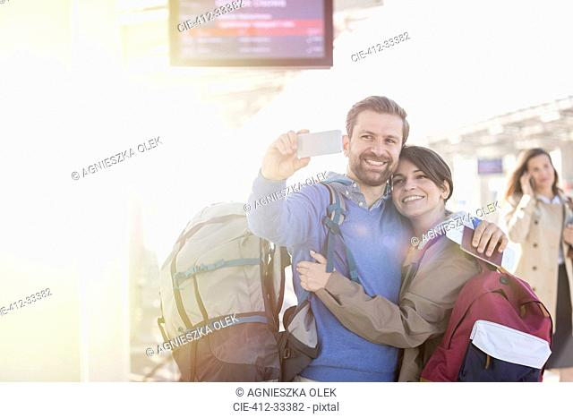 Couple with backpacks taking selfie at train station