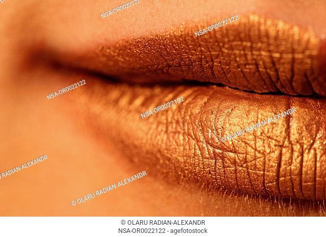 Macro blur image of bright lips - gold lipstik