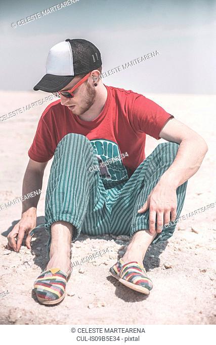 Man sitting on salt flats, touching salt, Jujuy, Salinas Grandes, Argentina