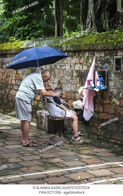 Street scene - barber cutting boy's hair, Old Quarter, Hanoi, Vietnam
