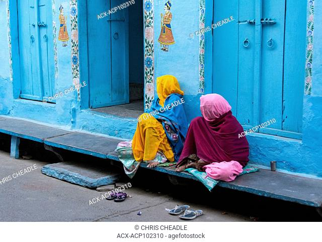 Two women and blue wall and doorways, Udaipur, Rajastan, India