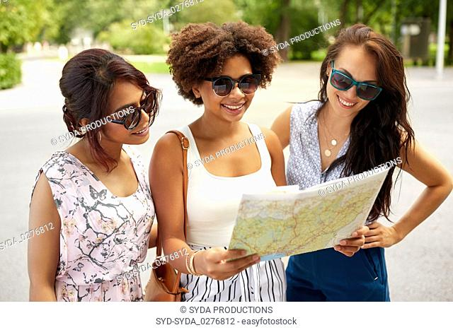 happy women with map on street in summer city
