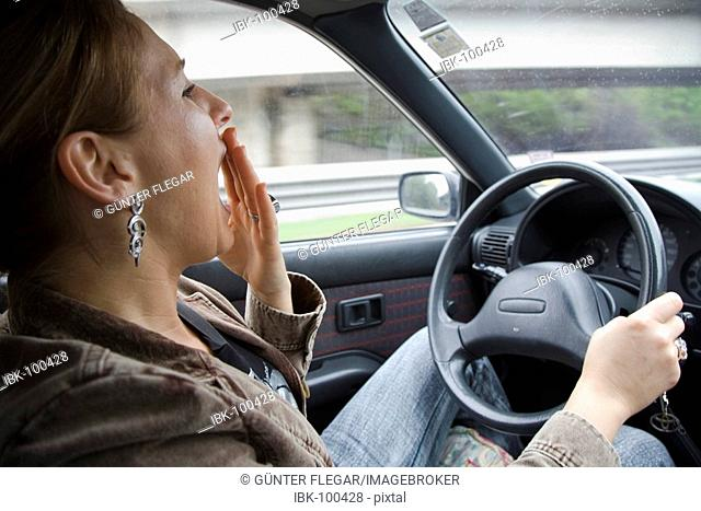 Symbol photo - Woman is in a tired way at the steering wheel