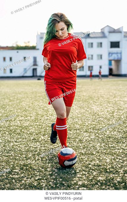 Young woman playing football on football ground running with the ball