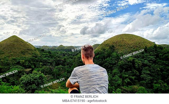 Young man looks at the Chocolate Hills on Bohol Island, Philippines