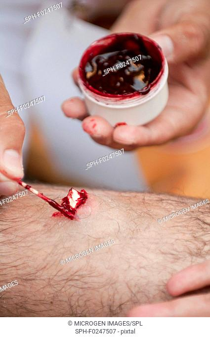 SFX make-up artist working on a leg fracture. Selective focus set on the wound