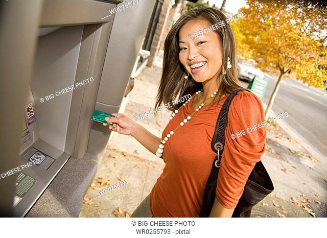 Woman smiling and using ATM