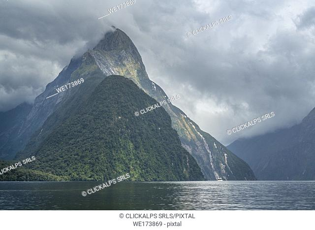 Boat and Mitre Peak under a moody sky in Milford Sound. Fiordland NP, Southland district, Southland region, South Island, New Zealand