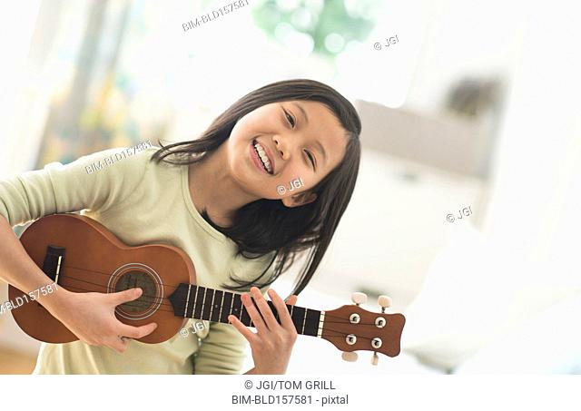 Chinese girl practicing ukulele in bedroom